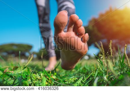 Barefoot Walking. Closeup Of Woman Running Barefoot In The Park On Green Grass