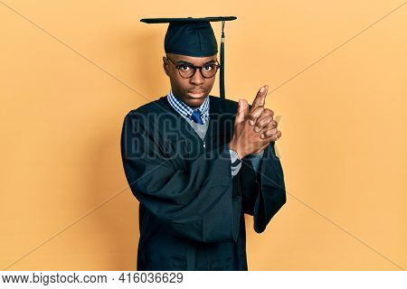 Young african american man wearing graduation cap and ceremony robe holding symbolic gun with hand gesture, playing killing shooting weapons, angry face