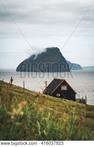 Black House On Famous Faroese Witches Finger Trail And Koltur Island On Background. Sandavagur Villa