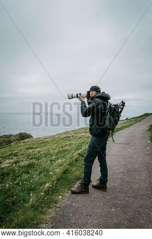 Young Man Trourist Traveler Hiking. Tjornuvik Beautiful Town In The Faroe Islands, Sit On The North