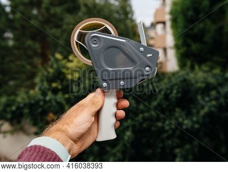 Point Of View Male Hand Holding Against Green Background New Tape Dispenser With Scotch Tape Adhesiv