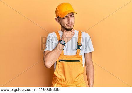Hispanic young man wearing handyman uniform touching painful neck, sore throat for flu, clod and infection