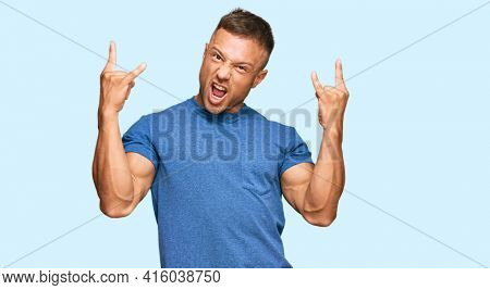 Handsome muscle man wearing casual clothes shouting with crazy expression doing rock symbol with hands up. music star. heavy concept.