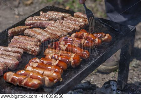 Male Hand Turning Delicious Grilled Meat By Fork. Man Preparing Bbq For Friends And Family. Bosnian