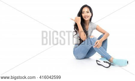 A Young Asian Woman Wore A Casual Dress Sit On The Floor. She Pointed Her Finger At The Copy Space O