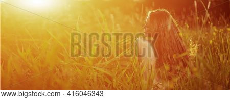 Casual Girl in field in Sunset in spring, summer landscape background Springtime