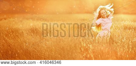 . Casual Girl in the field in Sunset in spring or summer landscape background.