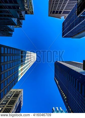 Clear Blue Sky Over Skyscrapers In Nyc, From An Upward Perspective On A Sunny Day. The Focus Is On T