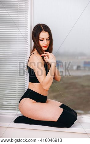 Young Woman Posing In Erotic Lingerie. Sexy Fashion Model In Dark Underwear. Passionate Woman In Bla