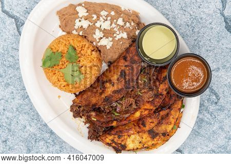 Overhead View Of Threesome Of Red Birria Tacos Fried To Perfection Served On A Plate With Rice Mound