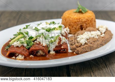 Chicken Enchiladas Smothered In Red Sauce Served With Refried Beans And Rice For A Tasty Mexican Foo