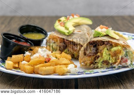 Avacado Slices Top Both Halves Of The Flavorful Mexican Breakfast Burrito Served With Cubed Potatoes