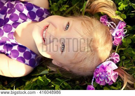 Beautiful little girl lying on the grass in the park. Smiling child on a field with flowers. Kid rest on the nature. Portrait of baby outdoor