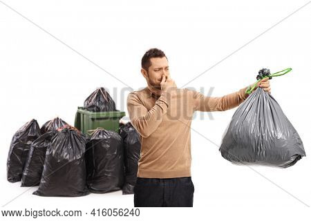 Young man holding a smelly garbage bag and covering his nose near a waste bin isolated on white background
