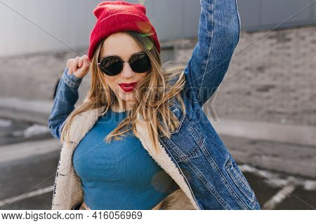 Amazing Young Woman Dancing On The Street With Kissing Face Expression. Outdoor Shot Of Beautiful Wh
