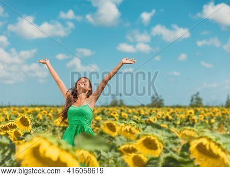 Happy free Asian woman dancing with arms up of hapiness in sunflowers field celebrating spring relaxing in the sun. Girl enjoying nature looking up sunbathing in fresh air.