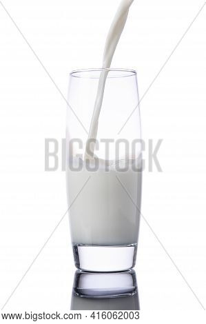 Pouring Milk Into A Glass, Isolated On White Background