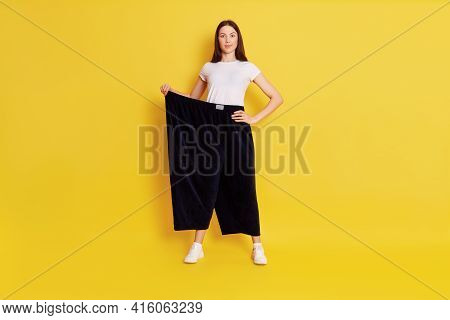 Dark Haired Caucasian Female In Too Big Size Trousers, Posing With Hand On Hip, Look At Camera With