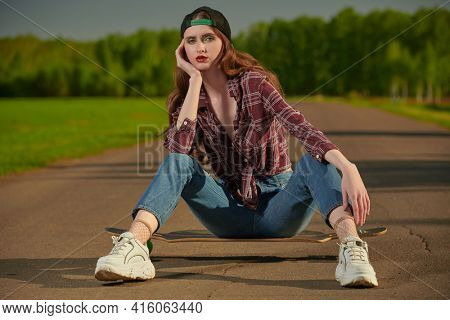 Cool modern teen girl sits with her longboard on a highway outside the city. Summer vacation in the country.