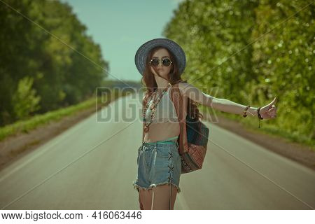 Skinny hippie girl with a guitar and a backpack hitchhiking on a highway. Spirit of freedom. Summer vacation adventure.