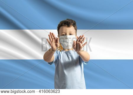 Little White Boy In A Protective Mask On The Background Of The Flag Of Argentina. Makes A Stop Sign