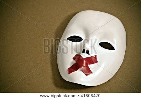 white mask with red tape strips forming a cross in its mouth on a brown background