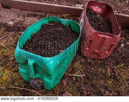 Two Plastic Cans Cut In Half And Reused And Repurposed As Flower Pots Or Planters Filled With Soil I