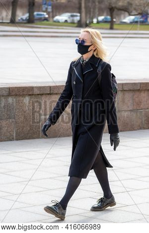 Vilnius, Lithuania - April 7 2021: Beautiful Blond Girl Dressing Black With Mask And Sunglasses Walk