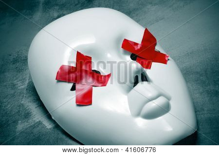 white mask with red tape strips forming crosses in its eyes on a blue background