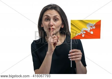 Happy Young White Woman Holding Flag Of Butane And Holds A Finger To Her Lips Isolated On A White Ba