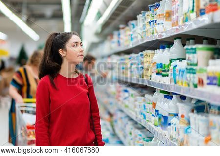 Shopping. Portrait Of A Young Pretty Woman Looking At The Display Cases With Dairy Products In The S