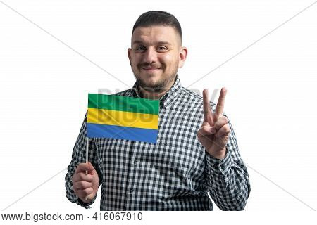 White Guy Holding A Flag Of Gabon And Shows Two Fingers Isolated On A White Background.