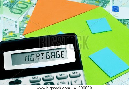 word mortgage written in the display of a calculator, and a depiction of a house on a pile of euro bills