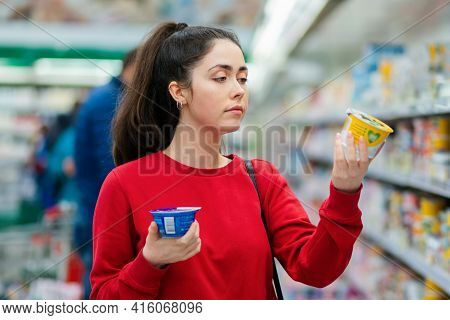 Shopping. Portrait Of A Young Pretty Woman Chooses Between Two Yogurts. The Concept Of Consumerism A