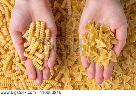 Different Varieties Of Pasta In Female Hands. Farfalle And Fusilli Pasta. Top View