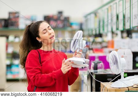 Portrait Of Young Pretty Woman Chooses A Mini Fan In A Home Appliance Store. The Concept Of Consumer