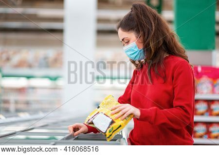 Antiviral Protection In Public Places. Portrait Of Young Woman In A Medical Mask Buys Frozen Food In
