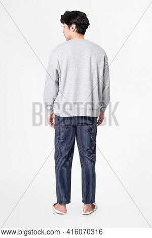Man in gray sweater and pants sleepwear apparel rear view