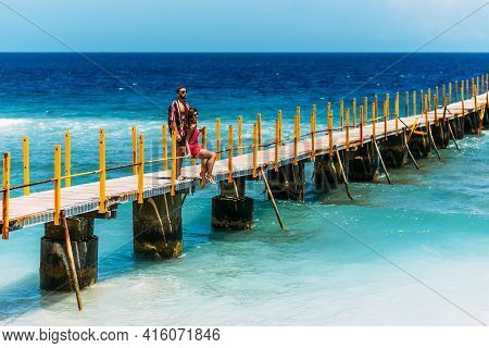 A Beautiful Couple On Vacation Strolling Along A Wooden Pier Above The Tropical, Turquoise Ocean In