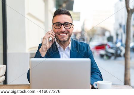 Businessman Having Phone Call In A Cafe Outdoors.