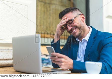 Businessman Using Using Cellphone While Working In A Cafe.
