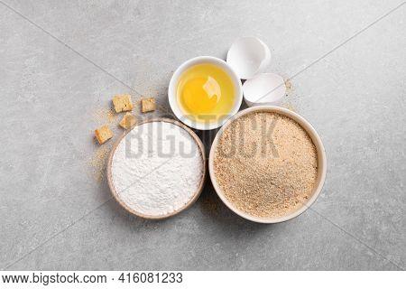 Fresh Breadcrumbs, Flour And Egg On Light Grey Table, Flat Lay