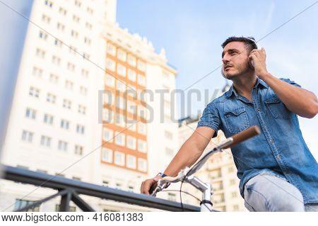 Latin American Man Listening Music Sitting On Bike Outdoors .