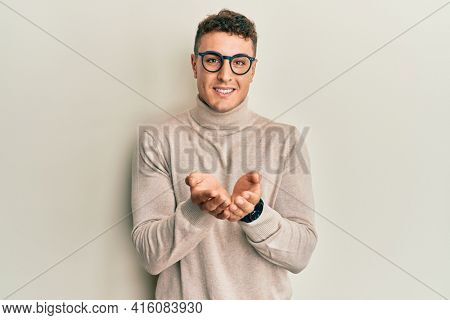 Hispanic young man wearing casual turtleneck sweater smiling with hands palms together receiving or giving gesture. hold and protection