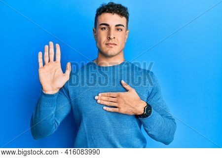 Hispanic young man wearing casual winter sweater swearing with hand on chest and open palm, making a loyalty promise oath