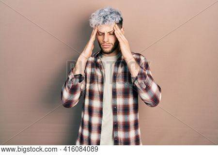 Young hispanic man with modern dyed hair wearing casual shirt suffering from headache desperate and stressed because pain and migraine. hands on head.
