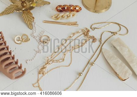 Modern Golden Jewellery And Hair Clips On White Wooden Table With Vintage Candlesticks. Stylish Gold