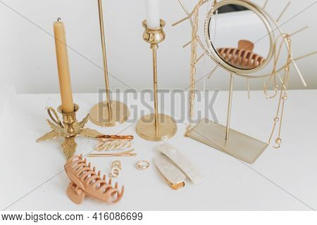 Modern Golden Jewellery, Hair Clips On White Table With Vintage Candles And Boho Mirror. Stylish Gol