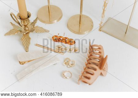 Modern Golden Accessories And Hair Clips On White Table With Vintage Candles And Boho Mirror. Stylis