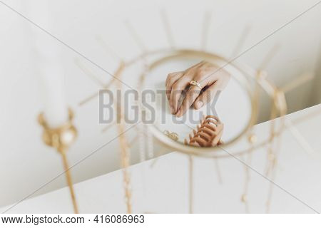 Female Hand With Modern Golden Ring And Earrings Reflected In Boho Mirror On White Table With Vintag